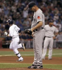 Sox starter Tim Wakefield is contemplative as the Rays' Evan Longoria rounds the bases after hitting a fourth-inning homer.