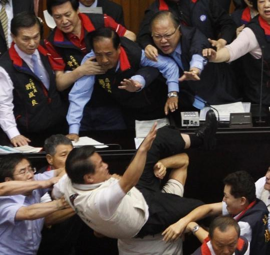 Kuo Wen-chen, a Democratic Progressive Party legislator, was tossed off the podium during yesterday's legislative scuffle.