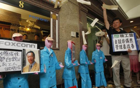 Labor activists threw paper money in front of cutouts representing Chinese employees during a protest outside the Foxconn Technology Group office in Hong Kong. Chinese factory workers have started demanding better wages and working conditions.