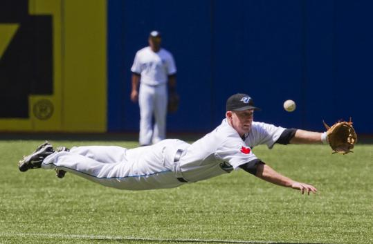 Blue Jays second baseman Aaron Hill dives for but misses a ball hit by the Red Sox' Bill Hall in the seventh inning, which went for a single.