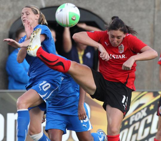 Atlanta's Rebecca Nolin puts her best foot forward and is able to clear the ball away from Kelly Smith of the Breakers.