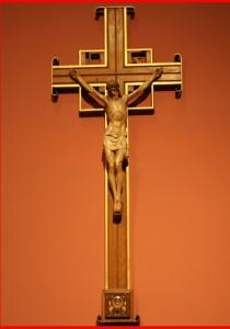 On the wall in the dim chapel hangs a cross with its base pried open and an empty cavity where the relic once rested.