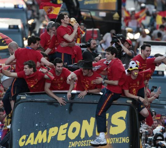 Spain's Iker Casillas kisses the World Cup trophy as the team celebrates its victory during a parade in Madrid.