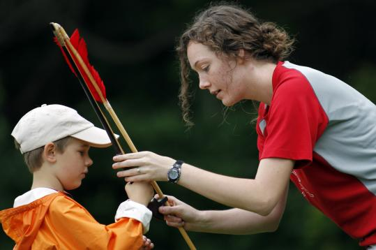 Devin Batchelder shows Boxford Cub Scout Will Kennedy, 8, how to hold and throw an atlatl in Boxford last month.