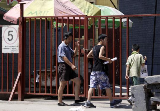 Residents approached a narrow entrance to a gated village on the outskirts of Beijing this month. Some say the gated villages are the latest indignity for China's migrant workers.