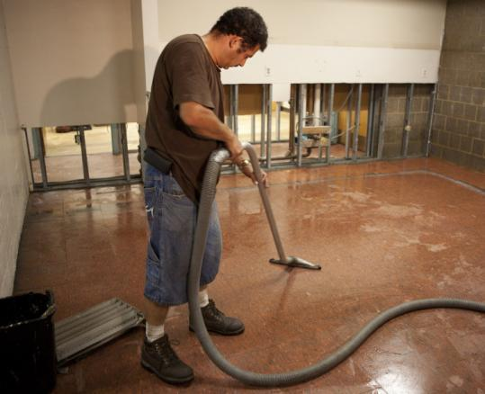 A clean-up worker vacuumed water at the Somerville public safety building earlier this week following Saturday's flooding.