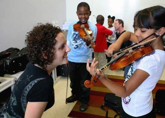 Rebecca Levi listens to Kayleen Guzman play at the Conservatory Lab Charter School in Brighton.