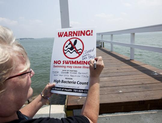 Terri Berardinelli updated a no-swimming sign in Hull yesterday, extending a high bacteria advisory until Wednesday.