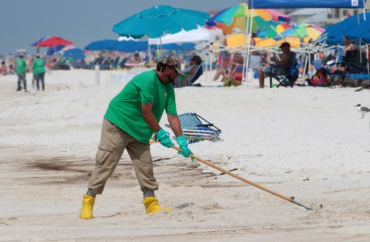 An oil cleanup worker raked the sand in Orange Beach, Ala., yesterday. BP officials said they do not agree with a US government strategy to ease pressure on the capped well by temporarily piping oil to the surface.