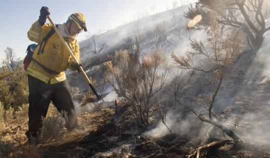 John McDonald, with the Pasco Fire Department, put out hot spots in a wildfire near Yakima, Wash., yesterday. Three other firefighters were injured trying to flee their trapped truck.