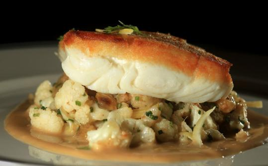 Halibut in a citrus-brown butter sauce with pine nuts, raisins, and cauliflower. .