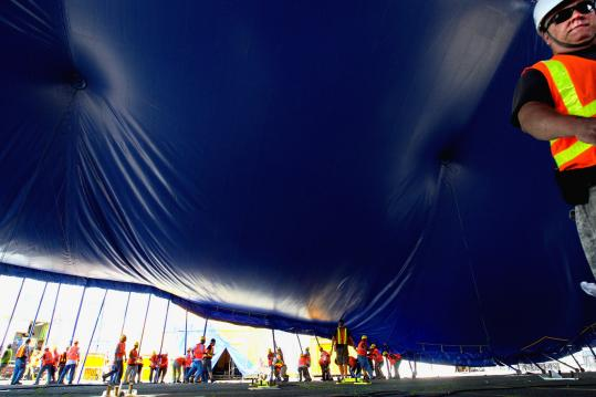 "Cirque du Soleil crew members raise the tent at Fan Pier last week as they set up the stage for ""OVO.''"