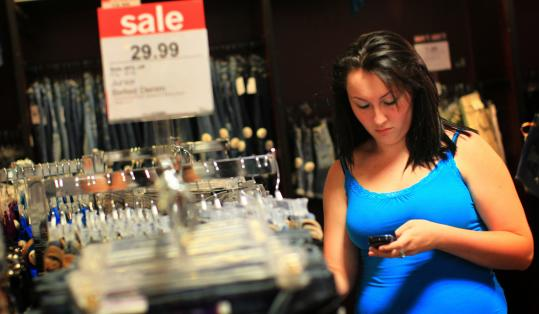 Alisha Beaulieu, 17, with her phone at North Shore Mall last week, could get coupons, sale alerts, and even make a purchase with it.