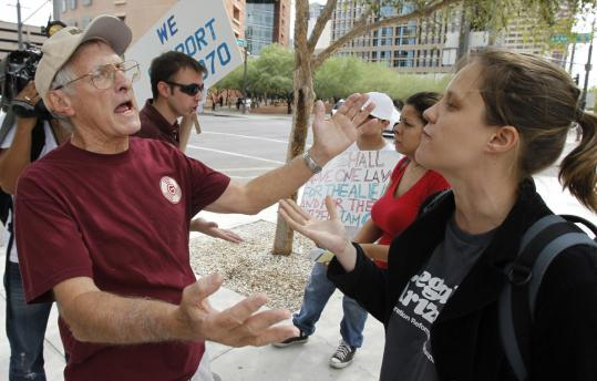 IMMIGRATION SHOWDOWN — Jerry Harris of Scottsdale, Ariz., a supporter of the state's immigration law, argued with Elizabeth Venable of Phoenix, who opposes it, outside US District Court in Phoenix yesterday. Judge Susan Bolton is considering whether the crackdown should take effect next week amid a flurry of legal challenges. A7.