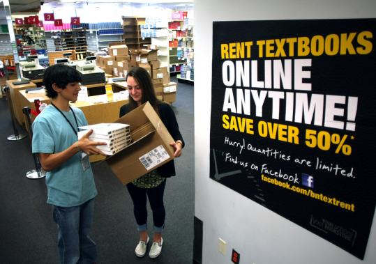 Isaac Tovares and Irene O'Brien stacked rental textbooks at the Boston University Barnes and Noble bookstore.