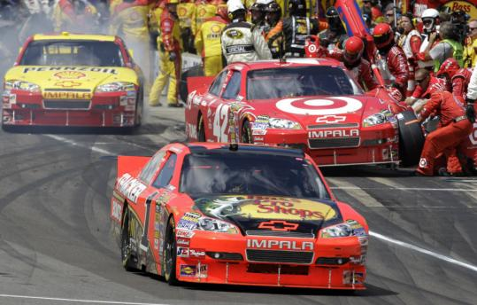 Jamie McMurray pulls out ahead of teammate Juan Pablo Montoya (42) during a late pit stop at the Brickyard. Montoya was leading the race prior to the stop. McMurray (below) has a Coke and a smile as he celebrates an improbable win on Victory Lane.