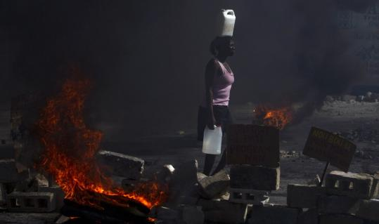 A woman walked past a burning barricade yesterday in Port-au-Prince during a protest alleging the Haitian government has not helped to rebuild the area after the Jan. 12 earthquake.