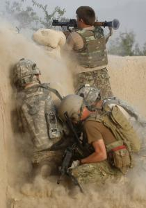 An Afghan soldier fired at suspected Taliban militants as US soldiers crouched beside him at an outpost in Kandahar Province. The Taliban said they killed a US sailor in a firefight.