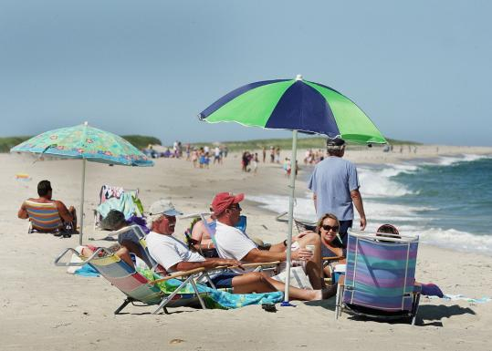 Beachgoers relaxed yesterday on South Beach, where swimming was banned after sightings of at least five distinct sharks.