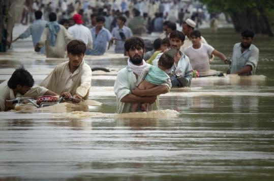 People waded through water while fleeing floods in Risalpur, Nowshera District, Pakistan. Hundreds of villages and towns were under several feet of water.