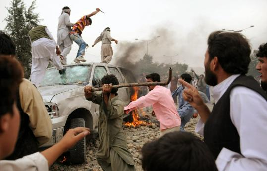 Protesters destroyed a car during clashes after four Afghans were stuck and killed by an SUV driven by US contract employees.