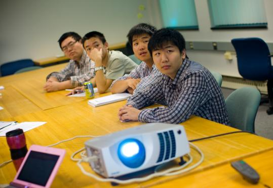 Owen Song (right) and other students at the Massachusetts International Academy in Marlborough focus on an English language skills presentation.