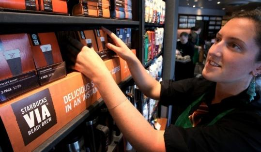 A Starbucks barista arranges a Via display at a store in Seattle. Via is available at about 37,000 US locations.