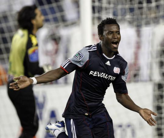 New England's Kenny Mansally celebrates his game-winning penalty kick against Puebla FC keeper Edgar Hernandez.