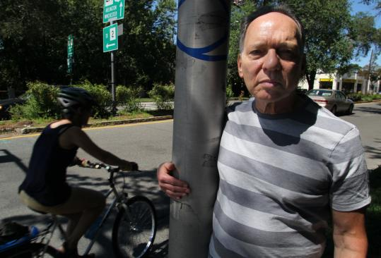 Eric Berger stood along Massachusetts Avenue, where town officials have proposed adding bike lanes. The 71-year-old Arlington resident has spent $40,000 of his own money in a fight against the plans.