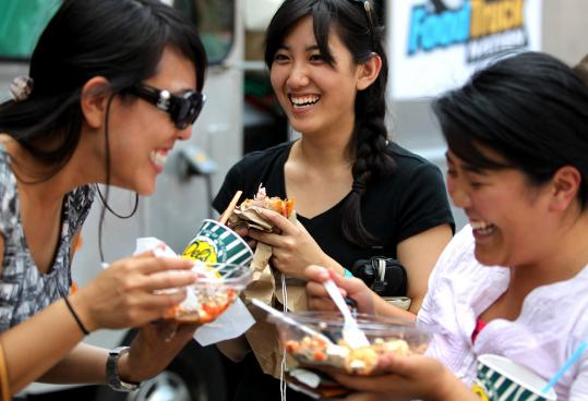 Jessica Cheng (left), Phoebe Kuo, and Maya Hartono, all of Cambridge, ate in line at the first Boston Food Truck Festival Sunday in the South End.