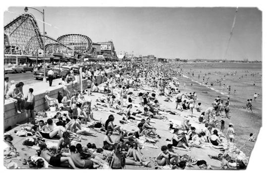 A mob of beachgoers in 1962 enjoy the beach and amusement park.