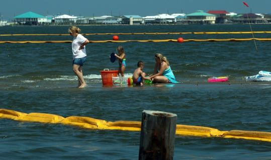 A family played near oil booms yesterday in Grand Isle, La. Officials were removing some booms that were put out to catch oil.