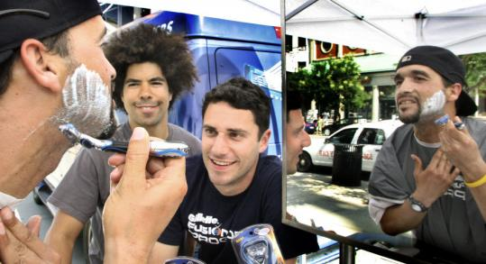 Angel Ortiz of Worcester tried out Gillette's new razor yesterday on Boylston Street with Gillette pitchmen Adam Ward (center) and Jason Zone Fisher.