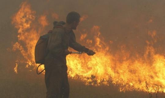 A firefighter worked to extinguish a blaze outside the town of Shatura, 68 miles southeast of Moscow, yesterday.