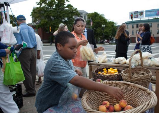 Makael Constance, 9, and his mother, Leslie-Ann Ogisde, shopped at a farmers' market yesterday. They are participating in a program aimed at making fresh food more affordable.