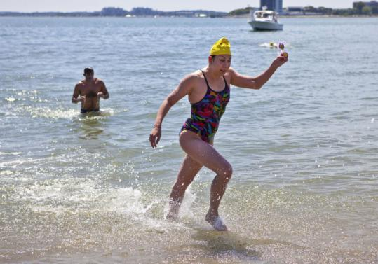 Elizabeth Mancuso splashed ashore and ran to the finish line to win the 8-mile race.
