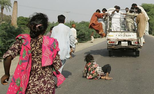 A woman fell off a truck distributing relief goods in Muzaffargarh, Pakistan. The nation is dealing with food shortages.