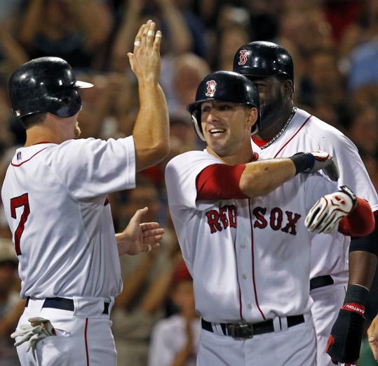 Ryan Kalish (right) is greeted by J.D. Drew and David Ortiz (rear) after belting a grand slam.