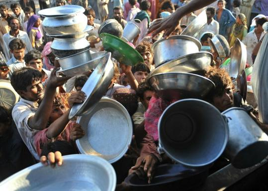 Flood victims competed for food supplies at a distribution point at an air force relief camp in Sukkur yesterday.