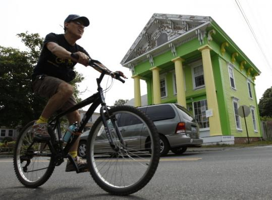 A cyclist rode past the historic Chatham house repainted fluorescent lime green and yellow, and has the town talking.