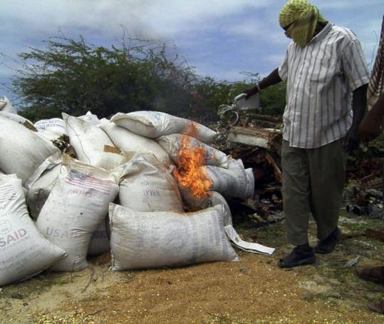 A member of Al Shabab burned bags of wheat bearing the US flag and the USAID stamp yesterday in Mogadishu, Somalia.