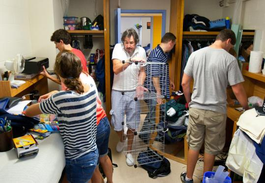 At Brandeis University yesterday, Lee Aaron of Fairfax, Va., squeezed through an already-crowded dorm room to bring in his son Dustin's shelving unit.