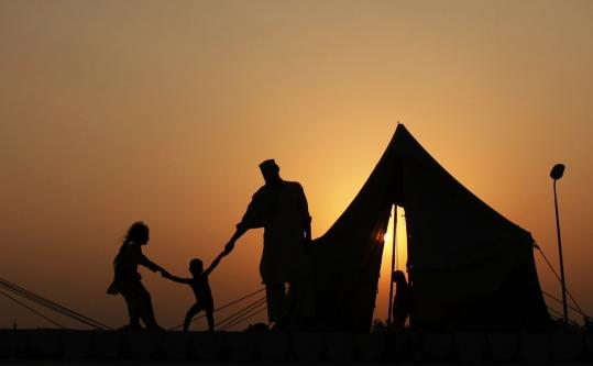 As the sun set yesterday, a Pakistani family waited for a food handout at a camp for flood victims on the outskirts of Peshawar.