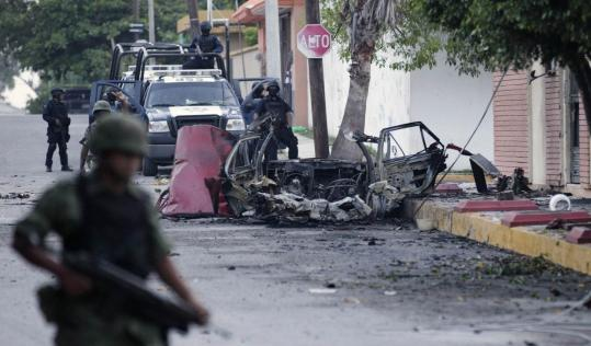 Mexican policemen and soldiers stood guard by the remains of a vehicle that exploded outside a television studio in Ciudad Victoria, Mexico. Another car exploded yesterday near the site of an investigation into the deaths of 72 migrants.