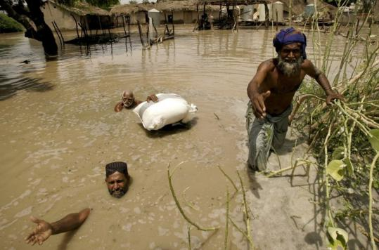 Pakistani flood survivors wait their turn to get relief food distributed by naval officials in Sangi Village near Sukkur, in southern Pakistan.