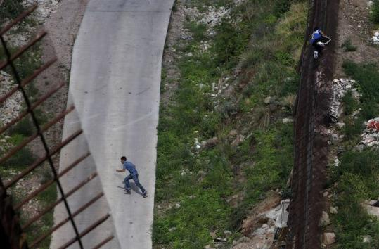 In July, migrants went over a border fence illegally in Nogales. With 59 deaths, the month was the second-deadliest recorded.