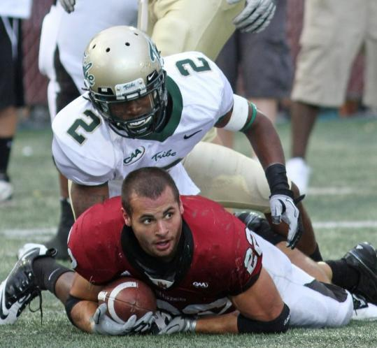 UMass tailback Jonathan Hernandez loses his helmet after this second-half tackle by William & Mary's B.W. Webb, but the Minuteman finished with 25 carries for 132 yards and a touchdown.