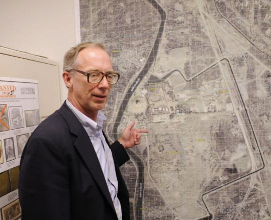 John Russell, a professor at the Massachusetts College of Art and Design, with a map of Babylon. Russell identified the 4,400-year-old statue of King Entemena after its recovery in 2006.