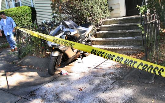 Police tape cordoned off the crime scene yesterday at 223 Salem St. in Malden, where a search warrant was later executed.