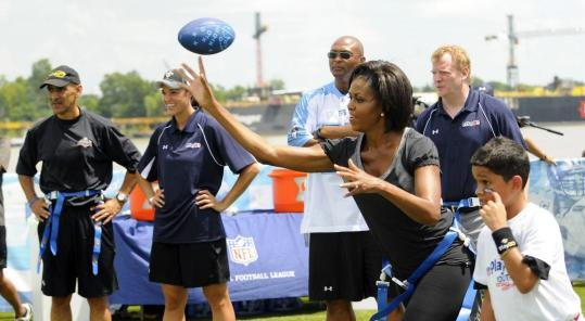 After getting the play call from Tony Dungy (left), Eddie George (center), and commissioner Roger Goodell (right), first lady Michelle Obama delivered a pass in New Orleans yesterday while helping the NFL encourage children to exercise daily.